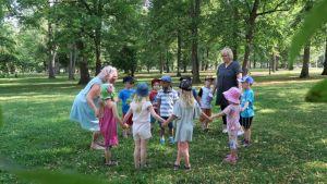 Lapsia ja päiväkodin työntekijöitä puistossa piirileikissä