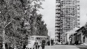 Kemin kaupungintalo harjannostajaispäivänä 23.9.1939. Kuva otettu Iso-Puistokatua (nyk. Meripuistokatu) itään päin. Rakennustyöt olivat vielä kesken. Kaupungintalo on kokonaan rakennustelineiden peitossa. Vasemmalla puolella näkyy linja-autoja Osuuskaupan aukealla. Kuvaaja: Väinö Pekkala.