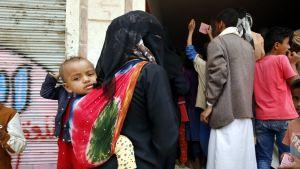 Ruokajono. Mustiin pukeutunut nainen seisoo jonossa kantaen lasta selässään.