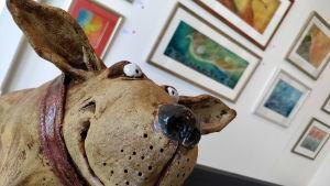 Koirapatsas naivisminäyttelyssä, patsaan takana tauluja