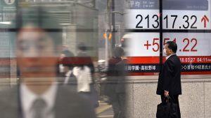Jalankulkija pörssikursseja näyttävän valotaulun edessä Tokiossa.