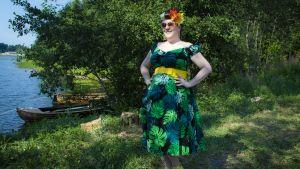 Pin-up tyylisesti pukeutunut nainen poseeraa ulkona.