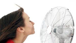 Nainen viilentää itseään tuulettimen edessä.