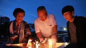 Ihmiset toivat kynttilöitä sukulaistensa muistolle Hiroshiman rauhanpuistossa 6. elokuuta.