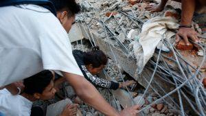 Paikalliset asukkaat etsivät eloonjääneitä romahtaneen rakennuksne raunioista Lombokin pohjoisosassa, Indonesiassa 6.8. 2018.