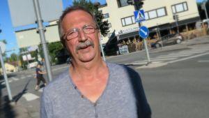 Mies seisoo kadunvarressa auringonpaisteessa
