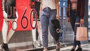 Nuoria naisia ostoskassit kädessä ostoskeskuksessa.