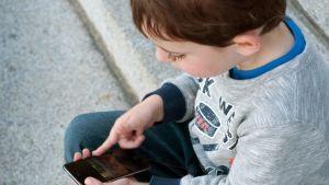 Lapsi käyttää mobiililaitetta.