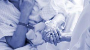 hoitaja pitää potilasta kädestä