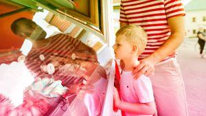 Poika isänsä kanssa ostamassa jäätelöä kioskista.