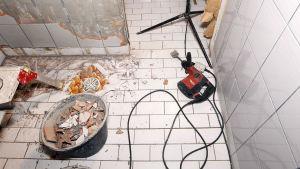 Kylpyhuoneremontti käynnissä. Työkaluja ja rikottuja laattoja kylpyhuoneen lattialla.