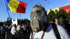 Mielenosoittajalla on kaasunaamari kasvojen edessä.