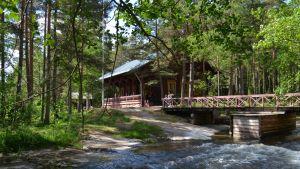 Kuohuva koski, jonka yli kulkee silta, jonka päässä on Langinkosken keisarillinen kalastusmaja.