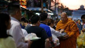 Ihmiset antavat ruokalahjoituksia buddhalaismunkille.