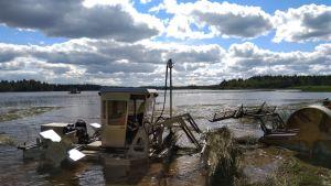 Vesikasvien niittämiseen tarkoitettu kone töissä rantavedessä.