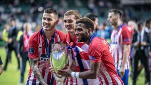 Atletico Madridin Antoine Griezmann, Thomas Lemar ja Lucas hernandez juhlivat Super Cupin voittoa pokaalin kanssa.