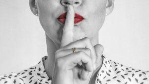 Nainen pitää sormea huulillaan