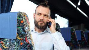 Mies kännykkä korvallaan bussissa.