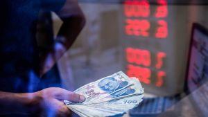 Valuutanvaihtovirkailija pitelee kädessään turkin liiroja.