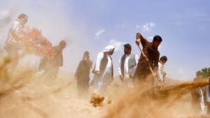 Miehet hautaavat itsemurhapommittajan uhreja Kabulissa 23. heinäkuuta.