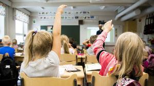 Kaksi lasta etualalla viittaavat oppitunilla.