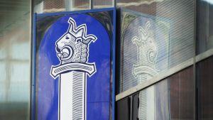 Poliisin logo poliisitalon seinässä.