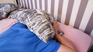 Mies sängyssä mahallaan ja pitelee tyynyä päänsä päällä.