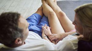 Mies ja nainen istuvat sohvalla toisiaan kädestä pitäen.