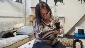 Satu Pöyhönen pitää sylissään harmaata muutaman viikon ikäistä kissanpentua.