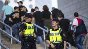 Kaksi naispoliisia seisovat portailla.