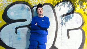 Rika Jylhä nojaa graffitiseinää vasten.