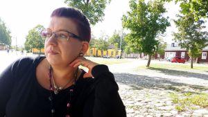 Piia Neuvonen istuu puistonpenkillä kertomassa tyttärestään