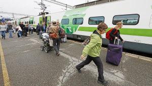 Junaan lähteviä matkustajia Joensuun asemalla.