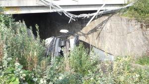 Linja-auto putosi kaiteen läpi junaradalle.
