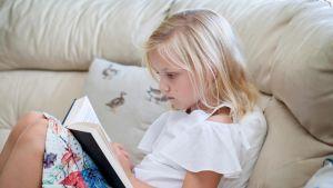 tyttö lukee sohvalla