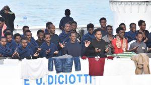 Siirtolaiset rukoilivat odottaessaan laivan kannella.