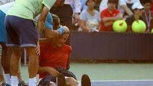 Mihail Jutshni istuu kentän pinnassa kuumuuden väsyttämänä.