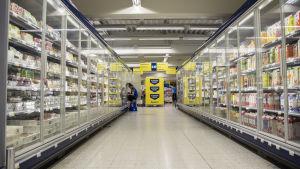 Kaupan käytävä, jonka molemmilla puolilla kylmäkaappeja täynnä tuotteita.