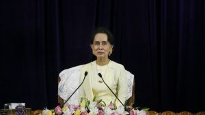 Aung San Suu Kyi istuu kukkalaitteen ja kahden mikrofonin takana vaaleankeltaisessa asussa tummaa taustaa vasten.