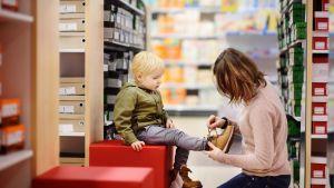 Äiti ja pikkupoika kenkäostoksilla.