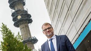 Juha Sipilä Ylen Mediatalon ja linkkitornin edessä.