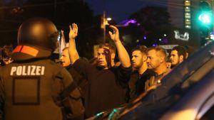 Kuvassa mielenosoittajat katsovat poliisia rauhallisesti. Poliisi selin kameraan kypärä päässään.