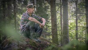 Mies istuu kivellä