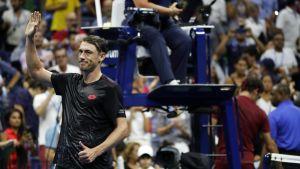 John Millman tuulettaa, Roger Federer taustalla.
