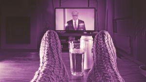 Televisio auki jossa näkyy tv-uutiset, katsoja kotona sohvalla jalat pöydällä ja pöydällä olutlasi.