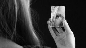 Nainen peili kädessään.