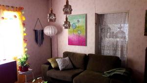 Vanhoja valaisimia, vihreä sohva ja taideteos olohuoneessa