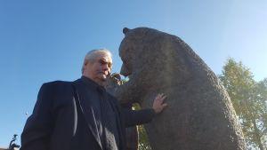 Sulo Karjalainen nojaa karhupatsaaseen.
