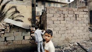 Jemeniläiset pikkupojat tutkivat palanutta taloa Sanaassa