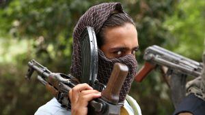 Entinen talebansotilas luovuttaa aseensa 3. syyskuuta Jalalabadissa osana rauhanprosessia.